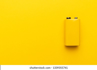 blank nine-volt battery on the yellow background with copy space