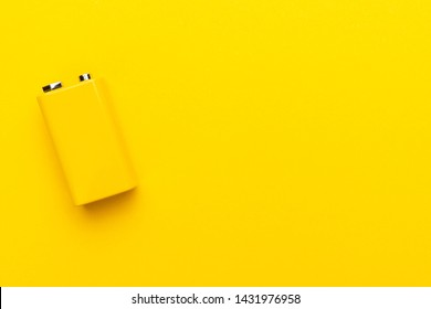 blank nine-volt battery on the yellow background with copy space. top view of yellow nine-volt battery. minimalist photo of blank battery