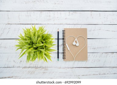Blank note book  for leave a message memo on white wooden background with green tree pots and headphone.