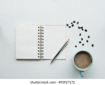 Blank note book, pen and coffee mug on white table working place. Flat lay