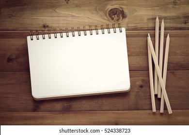 Blank note book and pencils on wood background, template with copy space for text