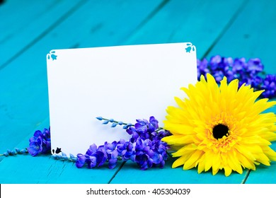 Blank note card with yellow sunflower and purple spring flowers on antique rustic teal blue wood background; springtime or Mothers Day background with white copy space