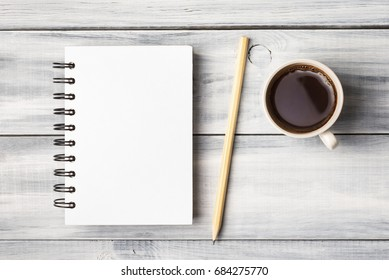 Blank note pad and coffee cup on white wooden table