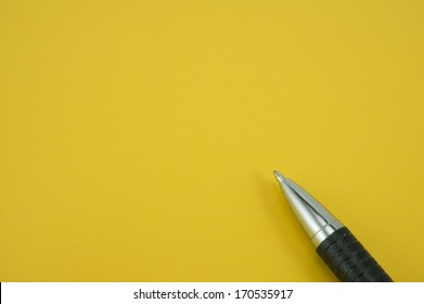 Blank  note with pen on yellow background