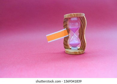 Blank note with sand clock for writing message on purple background