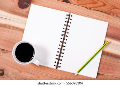 blank notebook with black coffee on wooden desk. Business style office working.