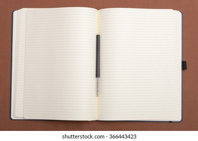 Blank notebook and black pen on brown background. Exercise book in line. Copybook with pen, top view.