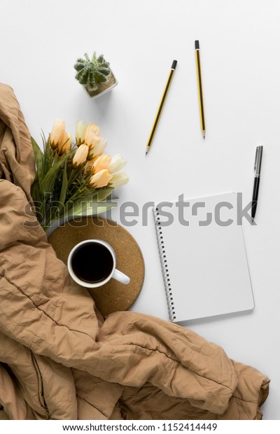 Blank notebook, coffee cup and sweater on neat white home office table.
