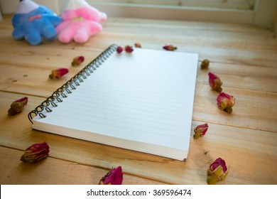 Blank notebook with copy space and rose put on the wood floor