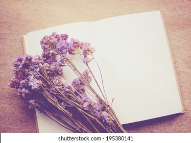 Blank notebook and dried statice flowers, nostalgic still life, retro instagram filter effect