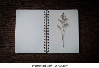 blank notebook with dry flower on wood table