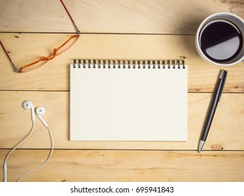 Blank notebook with earphone, pen, glasses & coffee on wooden table.