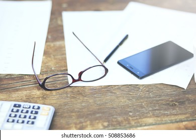 blank notebook with glasses and smartphone wood textures