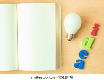 Blank of notebook, Lamp and Alphabet on wood background for idea creative concept and copy space