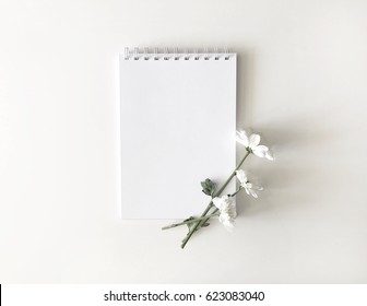 Blank notebook mockup with white daisy flower in minimal flat lay composition