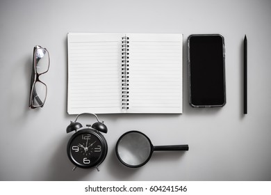 Blank notebook is on top of white office table.