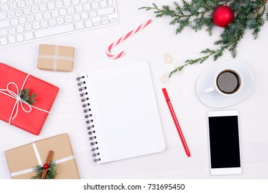 Blank notebook on white desk with Christmas decoration and presents