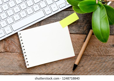 A blank notebook on the wood in the presence of a keyboard and a flower. View from above. High resolution photography.