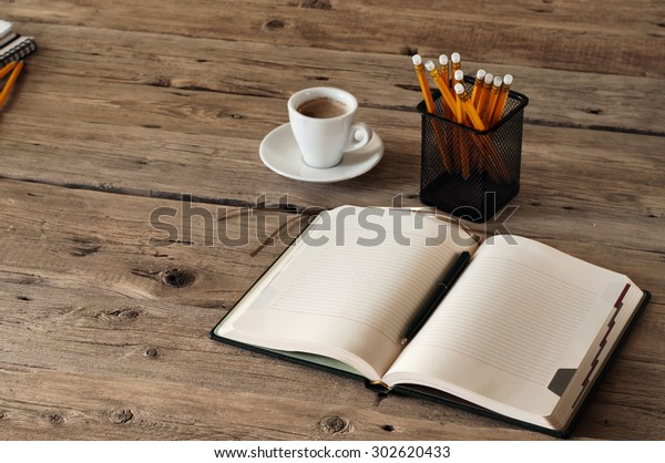 blank notebook on wooden table with a cup of black coffee and pencils. Closeup. View from above. Copy space. Free space for text