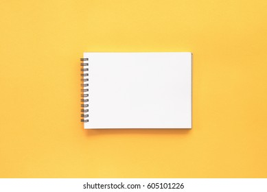 Blank notebook on yellow background.