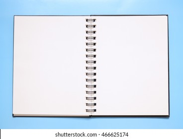A blank notebook open on a bright blue background