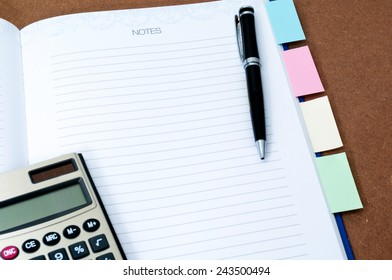 Blank notebook page with black ball pen, calculator and multi colored post it on wooden background
