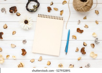 A blank notebook page and pen on white wooden table