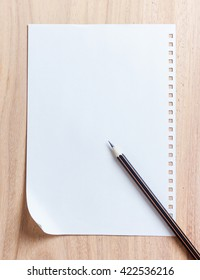 Blank notebook paper and pencil on wood table