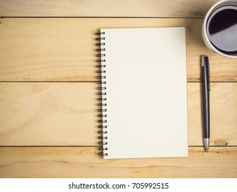Blank notebook with pen & coffee on wooden table.