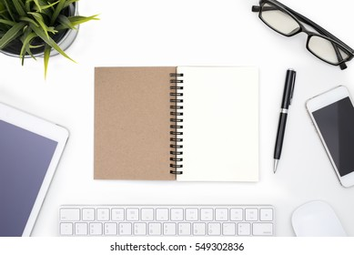 Blank notebook with pen, eye glasses, mobile phone, mouse, keyboard, tablet and small plant on white office table background with copy space view form above