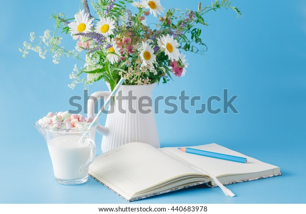Blank notebook with pen and flowers pot on blue background