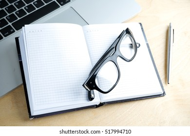 blank notebook, pen, glasses and laptop on the table