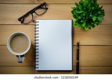 Blank notebook with pen and with glasses next to cup of coffee on wooden table,business concept.