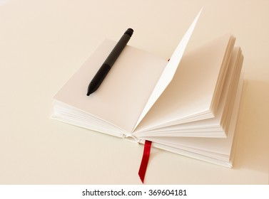 Blank Notebook with Pen Isolated on the White Background