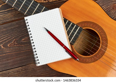 Blank notebook and pen on guitar. Acoustic guitar with notebook and pen on wood background.