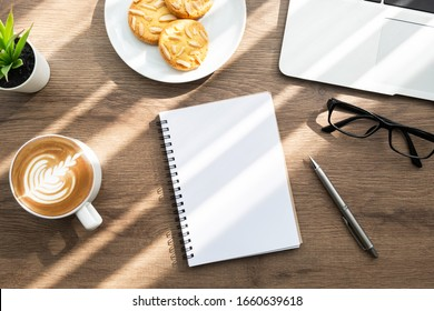 Blank notebook with pen are on top of wood office desk table with a dish of almond cookies, cup of latte coffee and office supplies, top view. Morning life at work concept.