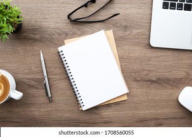 Leere Notebooks mit Stift befinden sich auf dem Schreibtisch aus Holz mit Laptop und Zubehör. Draufsicht mit Kopienraum. Morgenleben arbeitet von zu Hause Konzept.