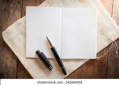 Blank notebook with pen on wooden table. The view from the top