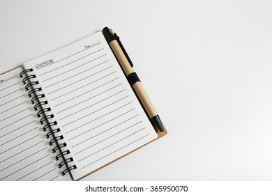 blank notebook with pen and pencil on white table