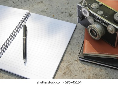 Blank notebook with pen and retro camera. Travel concept
