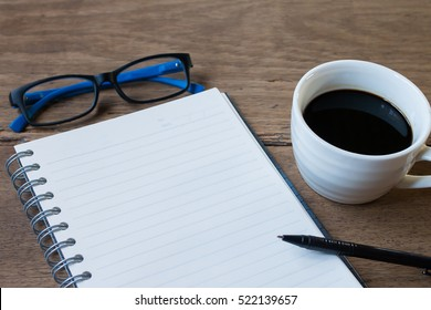Blank notebook with pencil and coffee on table background / selective focus, copy space