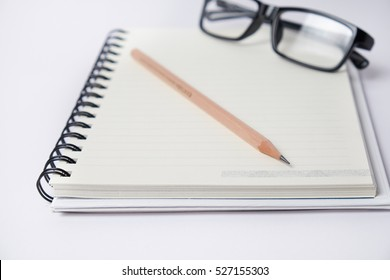 Blank  notebook with a Pencil and eyeglasses on white background, suit for writing and thinking concept.