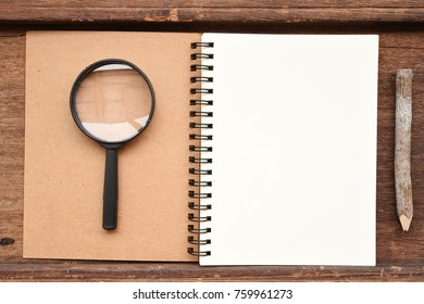 Blank notebook with pencil and magnifying glass on wooden background