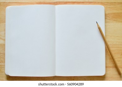 Blank Notebook with pencil on wood background.