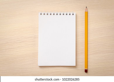 Blank notebook and pencil on wooden background