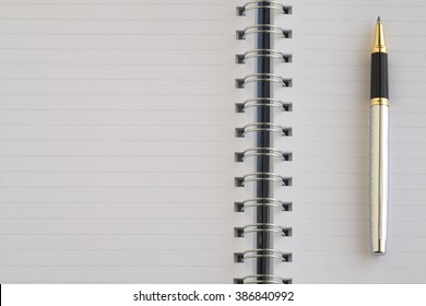 The blank notebook and a silver pen.