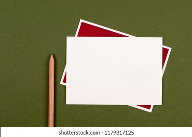 Blank notecard and pencil on green background