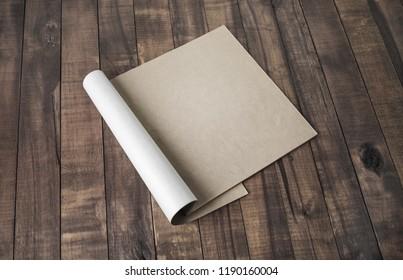 Blank notepad or brochure of kraft paper on vintage wooden background. Mockup for your design.