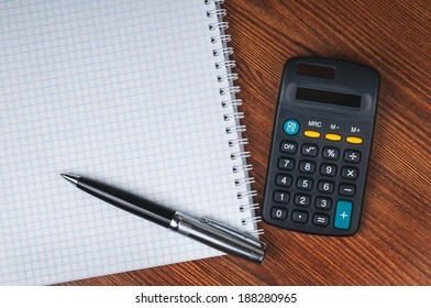 Blank notepad, calculator and pen laying on it on office wooden table