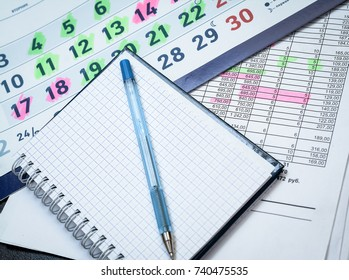 blank notepad with calendar and financial numbers table